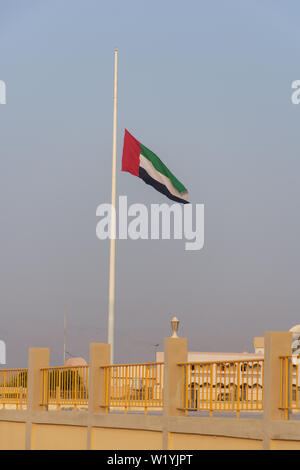 United Arab Emirates Flag flies at half mast due to mourning after the death of a ruler in the United Arab Emirates. - Stock Photo
