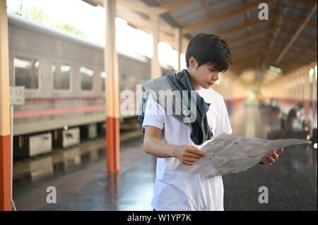 Man reading a map on train station with Travel asia concept. - Stock Photo