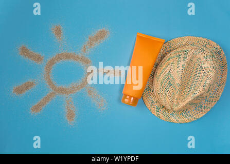 Sunscreens isolated on blue background. Sun drawn by the sand on blue background. Top view.