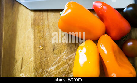 mixed paprika and tomatoes on a cutting board - Stock Photo