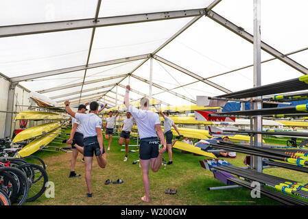 Henley on Thames, Berkshire, UK. 4th July, 2019. Henley Royal Regatta. Upper Thames  Rowing Club team limbering up with stretches in the boat tent before their race in the Thames Challenge Cup. Credit Gary Blake/Alamy Live - Stock Photo