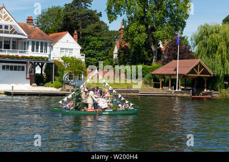 Henley on Thames, Berkshire, UK. 4th July, 2019. Henley Royal Regatta.Regatta spectators paddling a 'catamaran canoe' to moor up along  side  the wooden  boom separating the river traffic from the race on the River Thames  to view the afternoons  racing in style .Credit Gary Blake/Alamy Live - Stock Photo