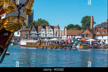 Henley on Thames, Berkshire, UK. 4th July, 2019. Henley Royal Regatta. 'Gloriana' the  90-foot-long British royal barge moored on the Thames river bank frames the rowers leaving the pontoon for the   Public Steamboat Alaska going past the backdrop of Henley town  Credit Gary Blake/Alamy Live - Stock Photo