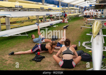 Henley on Thames, Berkshire, UK. 4th July, 2019. Henley Royal Regatta Girl competitors  limbering up with stretches in the boat tent before their afterrnoon race . Credit Gary Blake/Alamy Live - Stock Photo