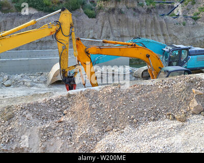 Two yellow and one blue excavators in the ditch at the site of the road construction works, side view, summer day. - Stock Photo
