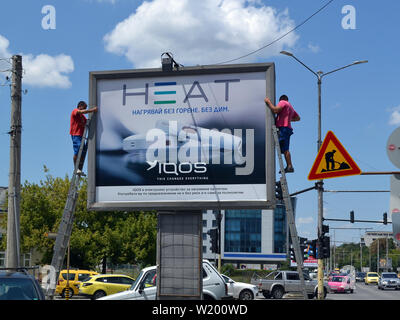 Varna, Bulgaria, July 2018. Two workers set an advertising poster for electronic cigarettes Iqos on a billboard near the road - Stock Photo