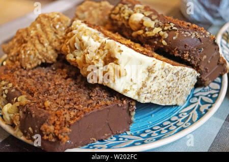 Christmas muffins with nuts and biscuits with powdered sugar on a decorative blue plate on the Christmas table - Stock Photo