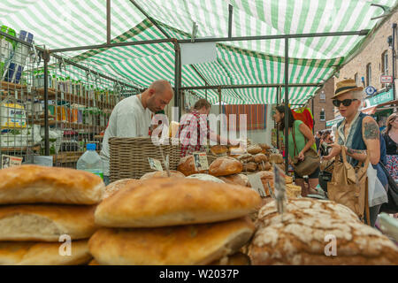 LONDON ENGLAND - JULY 13 2013; Buyers and vedors in bakery market stall in East London weekend market - Stock Photo