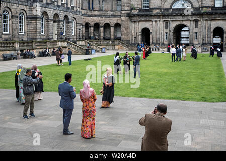 Asian students graduating from the University of Edinburgh pose for photographs with family and friends in the Quad of Old College on South Bridge. - Stock Photo