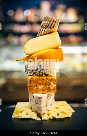 Assorted, various aged cheeses on plate or board. Different kind or type of delicious cheese on cheese platter. - Stock Photo
