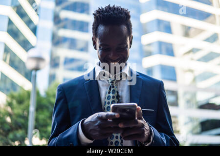 African American businessman holding mobile phone wearing blue suit - Stock Photo