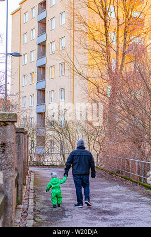 A father holds his son's hand as they take a walk along a path in Turku, Finland in Winter. - Stock Photo