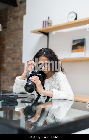 Young woman photographer processing pictures sitting on the desk - Stock Photo