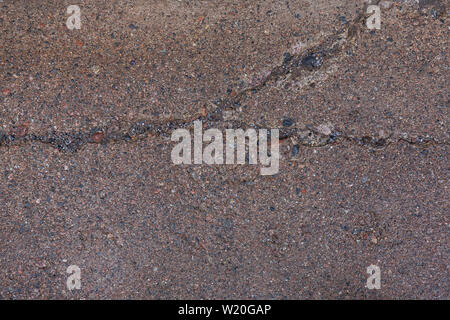 Close-up of a wet, weathered and cracked concrete footpath surface with pebbles (or pebblecrete or exposed aggregate) outdoors, viewed from above. - Stock Photo