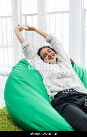 Young woman stretching while lying on the poof at home