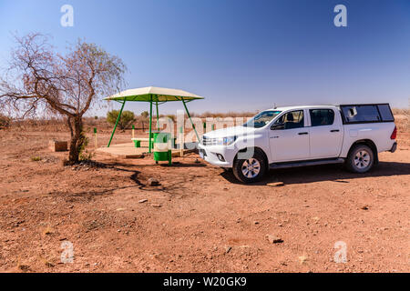 Toyota Hilux pick-up truck stopped beside a concrete picnic table and benches with a canopy for shade, typically placed every 10-20kms along roads in - Stock Photo
