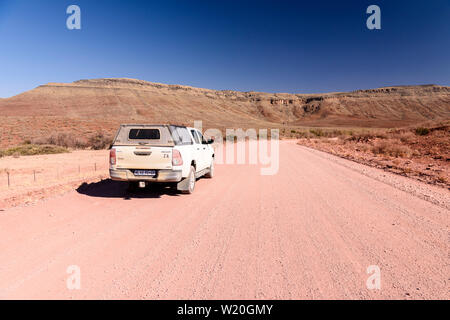 Toyota Hilux drives along a gravel dirt road leading towards mountains in Central Namibia - Stock Photo