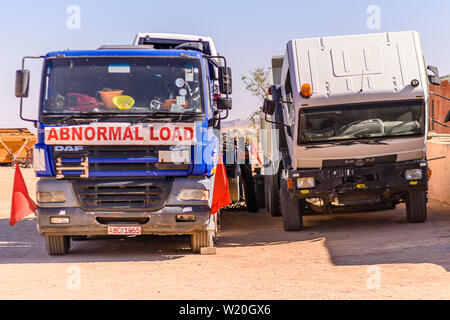 Trucks in c a car park, one with an 'Abnormal Load' sign, the other with the cab tipped to access the engine. - Stock Photo
