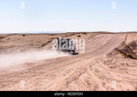 Toyota Hilux drives along a gravel dirt road leaving a dust trail in Central Namibia - Stock Photo