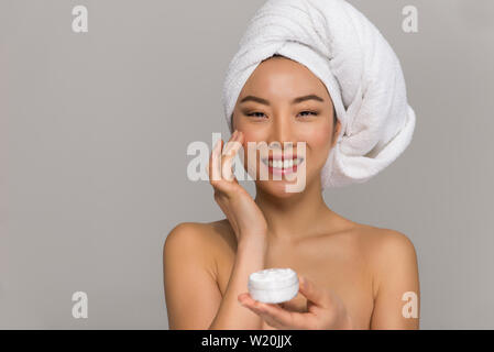 Beautiful asian woman beauty portraits. Chinese girl standing in front the mirror and taking care of her look. beauty studio shots Stock Photo
