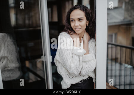 Shot of a Beautiful Brunette with Loose Hair Opening Doors of the Balcony and Walking onto Sunny Terrace with Seaside View. It's Cloudless Morning and - Stock Photo