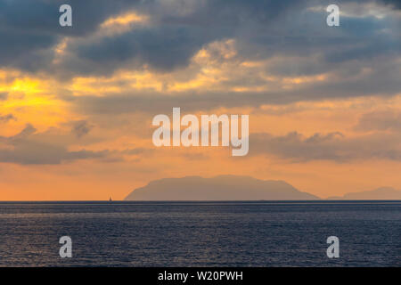 Picturesque sunset over Tyrrhenian Sea in Milazzo town, Sicily, Italy. Aeolian Islands (Italian: Isole Eolie), volcanic archipelago on the north of Si - Stock Photo