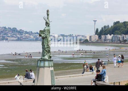 Alki's Lady Liberty presides over Alki Beach Park during an unusually low tide on Thursday, July 4, 2019 in Seattle, Washington. Tides reached the lowest tides of the year at -3.4 feet on Wednesday and Thursday. - Stock Photo