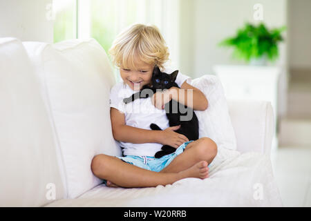 Child playing with baby cat. Kid holding black kitten. Little boy snuggling cute pet animal sitting on white couch in sunny living room at home. Kids - Stock Photo