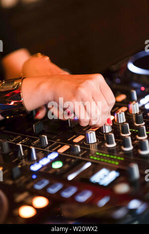 Detail of woman dj hands mixing on console. Close-up of music mixing equipment. - Stock Photo