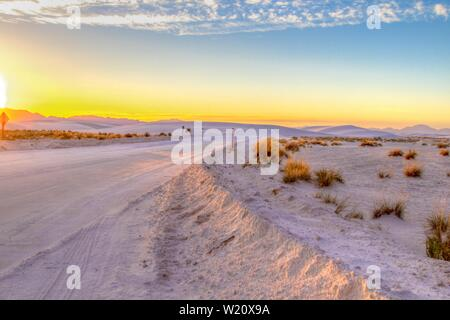 Desert Road Trip. Beautiful desert sunset with remote rural road winding through the sand dunes of the White Sands National Monument in New Mexico Stock Photo
