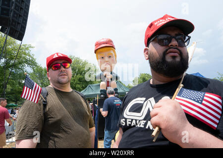 "Washington, United States Of America. 04th July, 2019. Motomoto and Christopher Casey, both of Brooklyn, New York, exchanged words with people who turned out to view the ""Baby Trump"" blimp and the Trump Tweeting statue in Washington, DC on July 4, 2019. Credit: Stefani Reynolds/CNP 