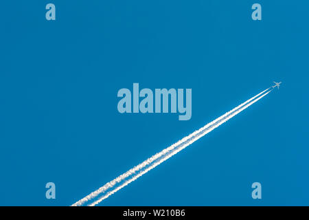 Airplane with white condensation tracks. Jet plane on clear blue sky with vapor trail. Travel by aeroplane concept. Trails of exhaust gas from plane - Stock Photo