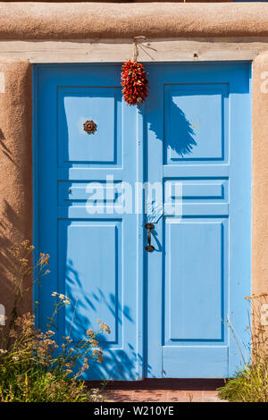 Ristra and blue door.  Ristra hanging in front of a blue door near Taos New Mexico.  Blue doors are thought to keep evil spirits away. - Stock Photo
