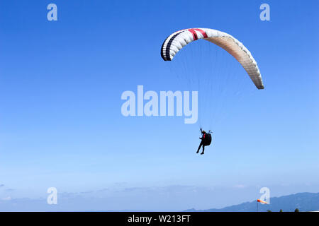 paraglider flying in blue sky on valleys landscape in Indonesia - Stock Photo