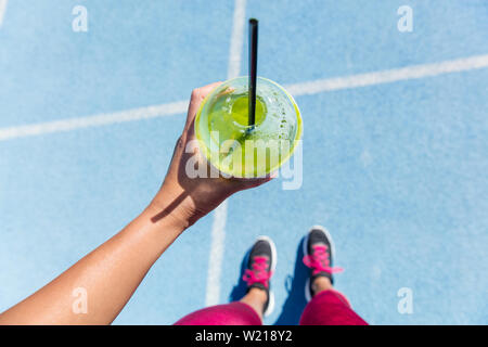 Runner drinking a healthy spinach green smoothie on outdoor running track getting ready for run. Closeup of hand holding juice drink on blue lane, social media health and fitness concept. - Stock Photo