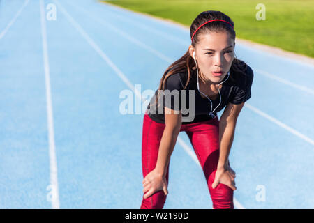Runner resting on outdoor running track tired taking a break getting determination and motivation ready for the challenge. Athlete woman listening to music with earphones for focus.