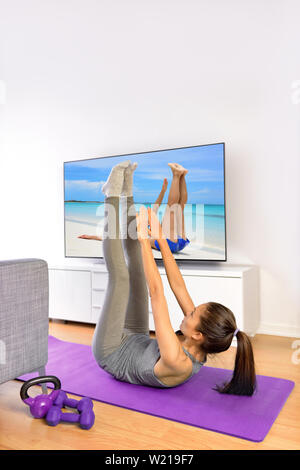 Home fitness ab workout in front of television. Girl doing toe touch crunch exercises to train upper abs for a flat stomach while watching a nature TV show or training program living a healthy life. - Stock Photo