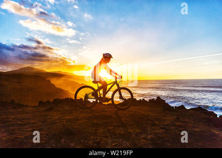 Mountain biking MTB cyclist woman cycling on bike trail on coast at sunset. Person on bike by sea in sportswear with bicycle enjoying healthy active lifestyle in beautiful nature. - Stock Photo