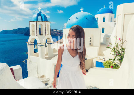 Santorini travel tourist woman on vacation in European destination walking on stairs. Asian girl in white dress visiting three blue domes in Oia village, greek island. Summer Europe holidays. - Stock Photo