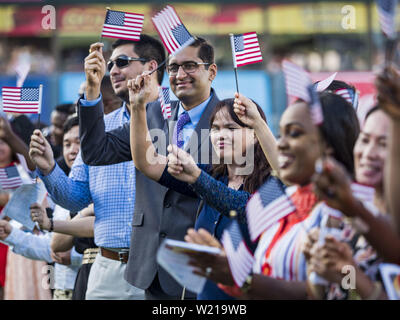 Des Moines, Iowa, USA. 4th July, 2019. Just naturalized American citizens wave their American flags after taking the Oath of Citizenship before the Iowa Cubs game. Thirty people became US citizens during a naturalization ceremony at the Iowa Cubs game in Des Moines. The naturalization ceremony is an Iowa Cubs 4th of July tradition. This is the 11th year they've held the ceremony. Credit: Jack Kurtz/ZUMA Wire/Alamy Live News - Stock Photo