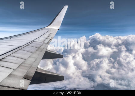 Amazing view of Dramatic clouds from window side seat of Airplane. Wings with its all components are visible. Clouds are fluffy as cotton balls. - Stock Photo