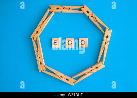 Wooden clothespins are scattered on a white and blue background with the words eco and natural. View from above. Copy space. Flat lay. The concept is - Stock Photo