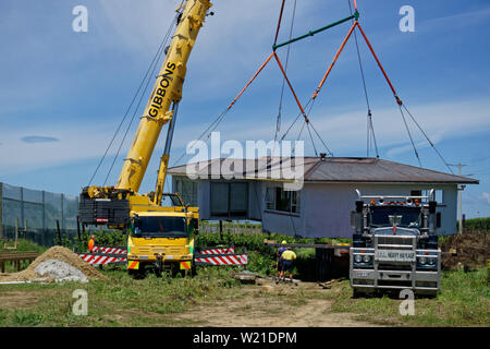 Motueka, Tasman/New Zealand - December 7, 2018: A house that has been sawn in two and moved to its new address being unloaded from a truck. - Stock Photo