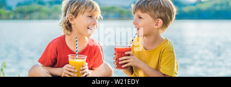 BANNER, LONG FORMAT Two boys drink healthy smoothies against the backdrop of palm trees. Mango and watermelon smoothies. Healthy nutrition and - Stock Photo