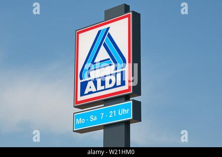 30.06.2019, the nameplate on an ALDI market in Schleswig. The neon sign of the discounters with the opening hours on a stele in front of bleuem sky.   usage worldwide