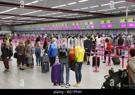 London Luton Airport, UK, check-in hall. Wizz Air passengers queue to check in for flights. Luton's check-in hall has 62 desks in a single line. - Stock Photo