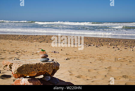 a pyramid of stones on a pebble beach against the sea and sky - Stock Photo