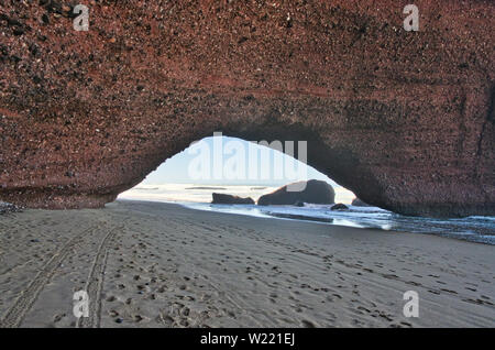 Red rock formation with arch on the beach, Plage Sidi Ifni, Morocco, Africa - Stock Photo