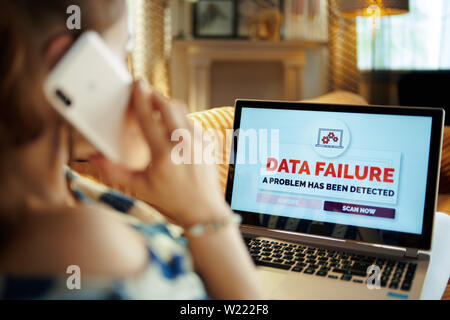 Over shoulder shot of modern woman laying on divan in the modern house in sunnny hot summer day having data failure and calling robot customer support - Stock Photo