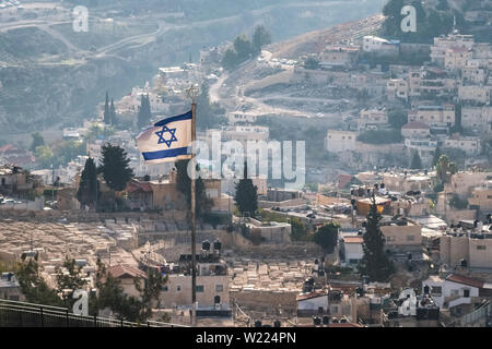 Israeli flag with residential buildings at background in Jerusalem, Israel - Stock Photo